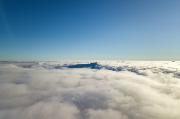 Widok z góry białe chmury podpuchnięte i odległy szczyt góry w jasny, słoneczny dzień.