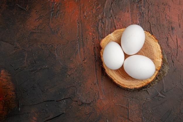 Widok z góry białe jaja kurze na ciemnym stole mączka zwierzęca jedzenie kolor zdjęcie surowe gospodarstwo wolna przestrzeń