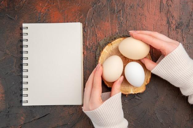 Widok z góry białe jaja kurze na ciemnym stole posiłek kolor zwierząt surowe zdjęcie jedzenie śniadanie