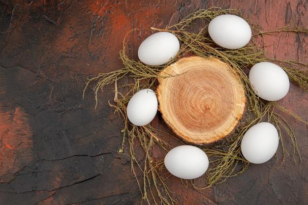 Widok z góry białe jaja kurze na ciemnym stole zdjęcie mączka zwierzęca jedzenie kolor surowe gospodarstwo wolna przestrzeń