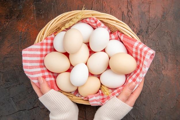 Widok z góry białe jaja kurze w koszu z ręcznikiem na ciemnym stole