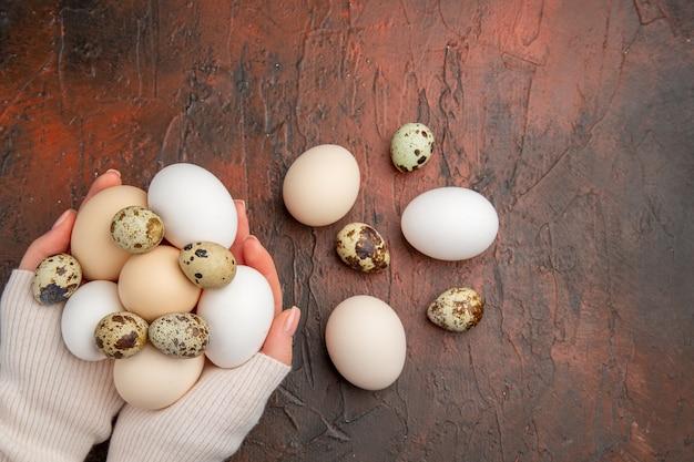 Widok z góry białe jaja kurze w rękach kobiet na ciemnym stole
