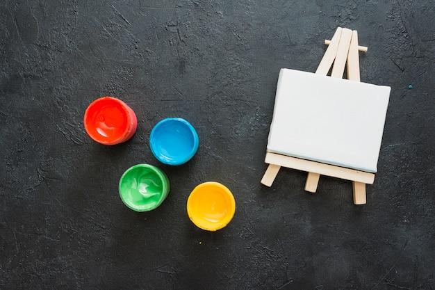 Widok z góry białe miniaturowe sztalugi i mały pojemnik z farbą