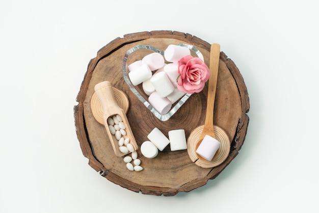 Widok z góry białe pianki pyszne i słodkie na brązowym drewnianym biurku, na białym biurku, cukier słodkie cukierki