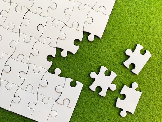 Widok z góry, białe puzzle na zielono