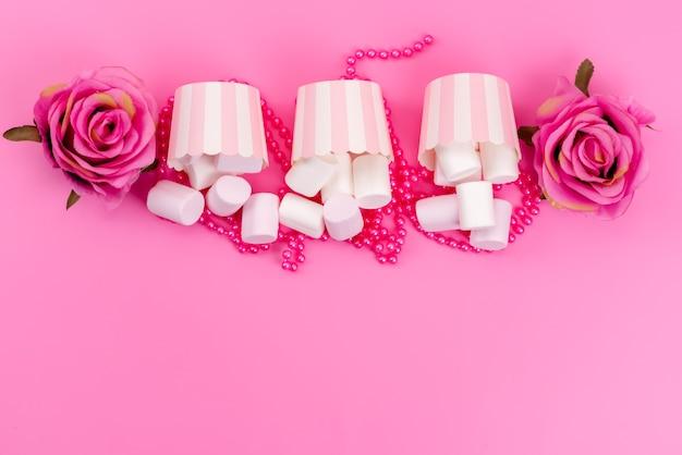 Widok z góry białe smaczne pianki marshmallows w papierowych opakowaniach z różowymi różami na różowym biurku, słodka biszkoptowa beza