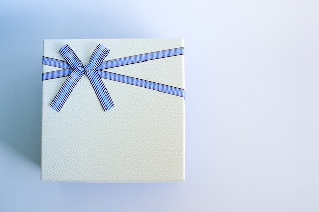 Widok z góry białego pudełka lub opakowania z niebieską wstążką i kokardą