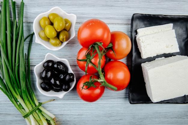 Widok z góry białego sera ze świeżymi pomidorami, zieloną cebulą i marynowanymi oliwkami