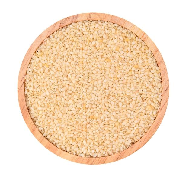 Widok z góry białego sezamu w drewnianym kubku na białym tle