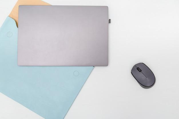 Widok z góry białego stołu roboczego z nowoczesnym laptopem, niebieskim skórzanym etui i myszą bezprzewodową. przestrzeń do pracy