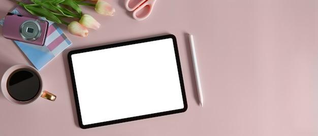 Widok z góry białego tabletu komputerowego z pustym ekranem kładzie się na stole otoczonym różnymi kobiecymi urządzeniami.