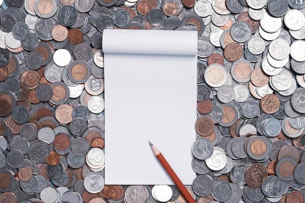 Widok z góry białej księgi z czerwonym ołówkiem na stosie monet