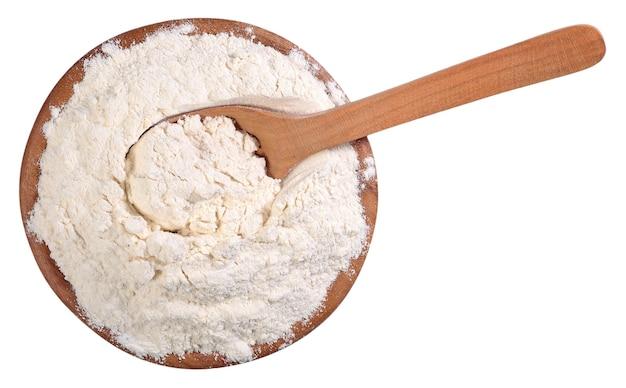 Widok z góry białej mąki w drewnianej misce z łyżką na białym tle