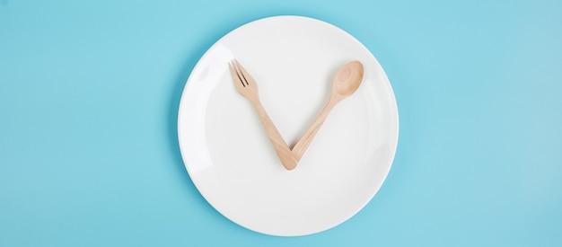 Widok z góry biały ceramiczny talerz z nożem, łyżką i widelcem na niebieskim tle. okresowy post, dieta ketogeniczna, odchudzanie, plan posiłków i koncepcja zdrowej żywności