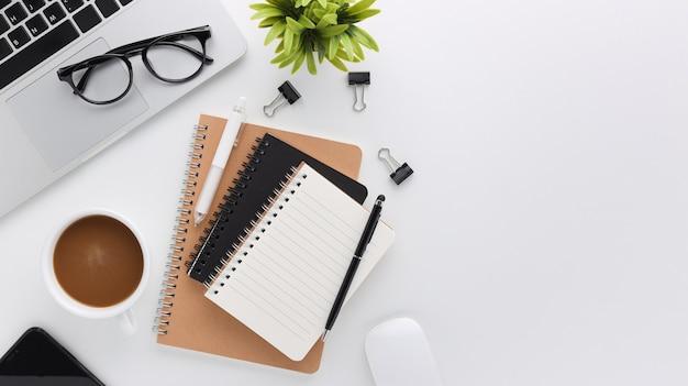 Widok z góry biały drewniany obszar roboczy biurko z komputerem i materiałami biurowymi. płaski stół roboczy z pustym notatnikiem, klawiaturą, zielonym liściem i filiżanką kawy. skopiuj miejsce na treści reklamowe.
