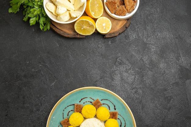 Widok z góry biały ser z cukierkami do ciasta i plasterkami cytryny na ciemnej powierzchni mączki owocowej żywności mlecznej