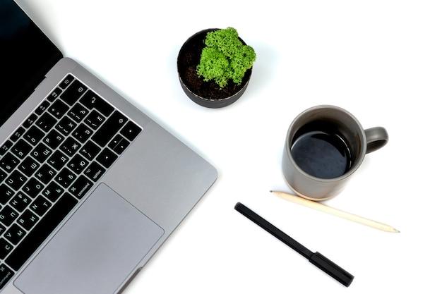 Widok z góry biały stół biurowy z pustym notatnikiem, klawiaturą laptopa, długopisem, rośliną i innymi materiałami biurowymi. z miejsca na kopię, leżał płasko, na białym tle. filiżanka kawy