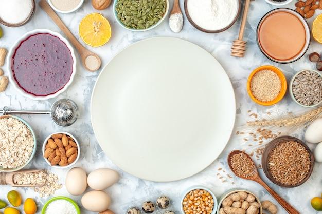 Widok z góry biały talerz miski z migdałami ziarna kukurydzy orzeszki ziemne ziarna pszenicy sezam jajka miód pałeczka jajka przepiórcze