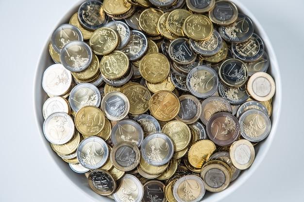Widok z góry biały talerz pełen monet euro.