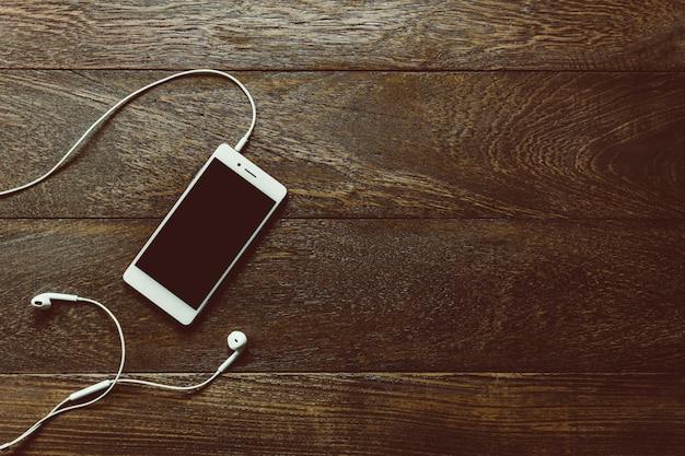 Widok z góry biały telefon komórkowy ze słuchawkami na biurku i miejsce.