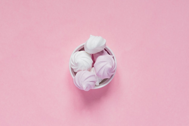 Widok z góry białych i różowych bezy w porcelanowej misce na różowo