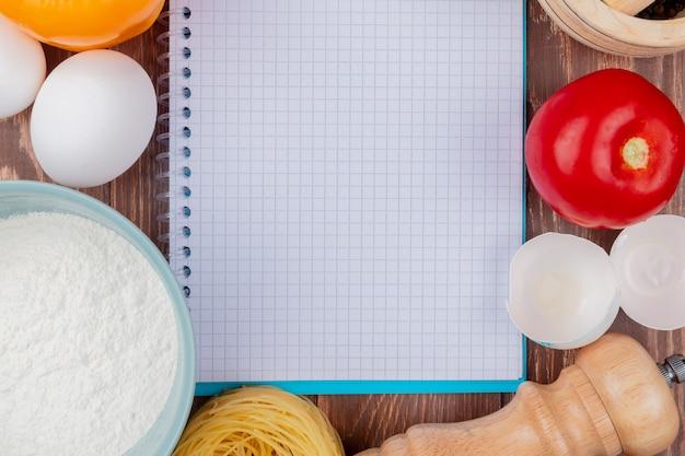 Widok z góry białych jaj kurzych z mąki na niebieskiej misce ze skorupkami jaj na tle drewnianych z miejsca na kopię