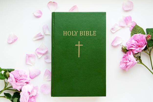 Widok z góry biblia i kwiaty z płatkami róż