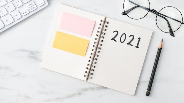 Widok z góry biurka biurko 2021 koncepcja pracy celu z klawiaturą, notatnikiem, ołówkiem, okularami i kawą