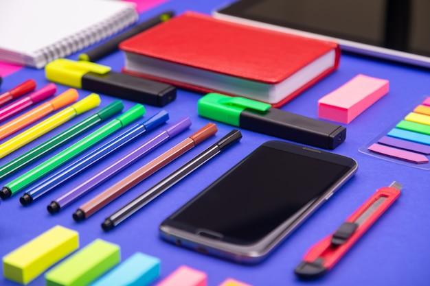 Widok z góry biurka biznesowego złożonego ze smartfona, kalkulatora, naklejek i kolorowych piór różowego i niebieskiego