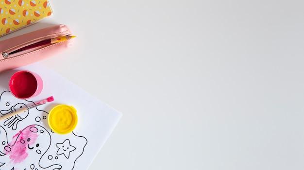 Widok z góry biurka dziecięcego z farbą i rysunkiem
