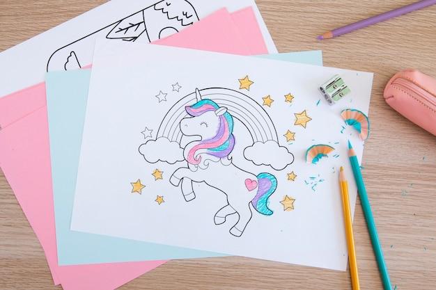 Widok z góry biurka dziecięcego z rysunkami i ołówkami