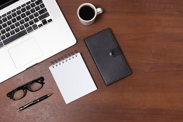 Widok z góry biurka z gorącą herbatą; pusty spiralny notatnik; dziennik; okulary; pióro i laptop