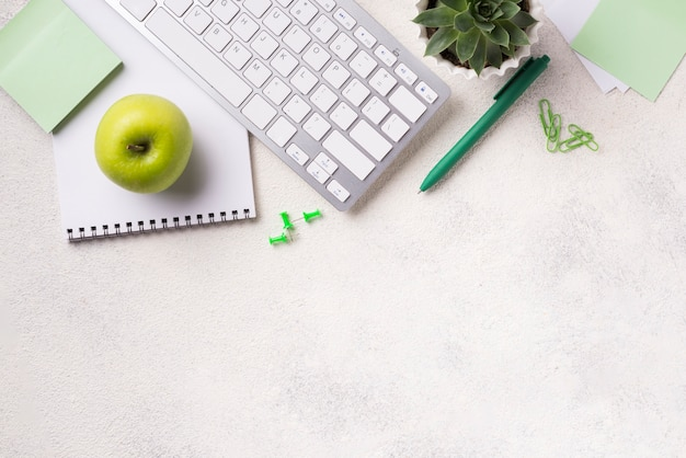 Widok z góry biurka z klawiaturą i jabłkiem
