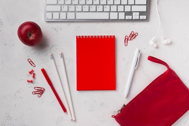 Widok z góry biurka z klawiaturą i notatnikiem