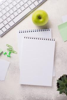 Widok z góry biurka z notatnikami i jabłkiem