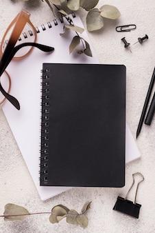 Widok z góry biurka z notebookami i okularami
