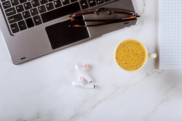 Widok z góry biuro pracy biurowej z laptopa, notatnik, szklanki i kawa, bezprzewodowe słuchawki, okulary