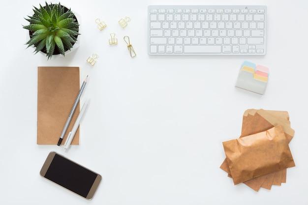 Widok z góry biurowego miejsca pracy z klawiaturą komputerową, notatnikiem, zielonym kwiatem doniczkowym, kopertami rzemieślniczymi i telefonem komórkowym, leżał płasko.