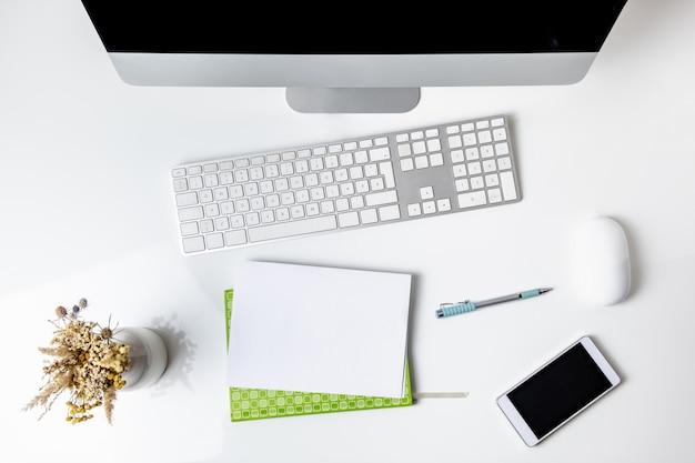 Widok z góry biurowego miejsca pracy z komputerem stacjonarnym. płaski układ komputera, telefonu komórkowego i klawiatury numerycznej na czystym białym stole