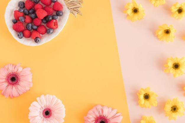Widok z góry biurowy letni stół biurkowy z kwiatami i jagodami w talerzu ananasa na pastelowym żółtym i różowym tle. przerwa w pracy, koncepcja lato. leżał płasko.