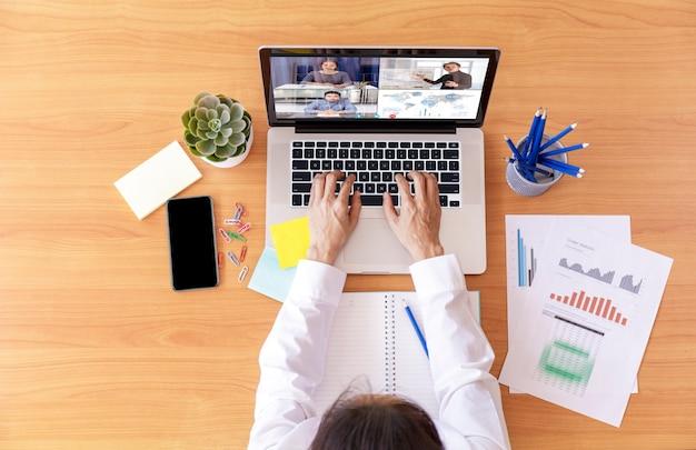 Widok z góry biznesmen i bizneswoman analizują wykres finansowy z wideokonferencją spotkania online.