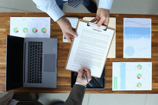 Widok z góry biznesmen podpisanie umowy ręka. biznesmeni dokonujący dochodowych transakcji międzynarodowych. laptop, dokumenty z danymi statystycznymi w miejscu pracy. koncepcja spotkania i negocjacji