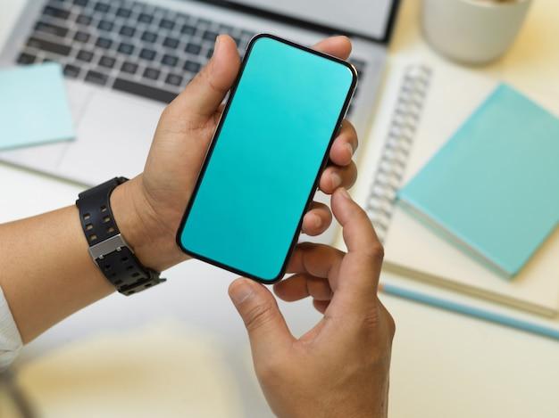 Widok z góry biznesmen ręce trzymając smartfon na siedząc w miejscu pracy