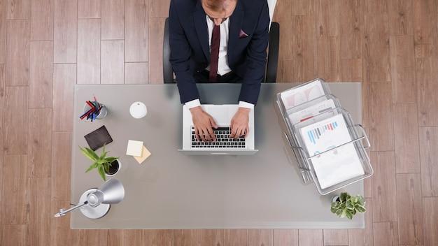Widok z góry biznesmena wpisującego strategię zarządzania na laptopie analizującego zysk firmy