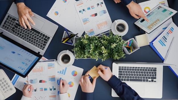 Widok z góry biznesmena wprowadzającego karteczki samoprzylepne na biurko wyjaśniające dokumenty finansowe