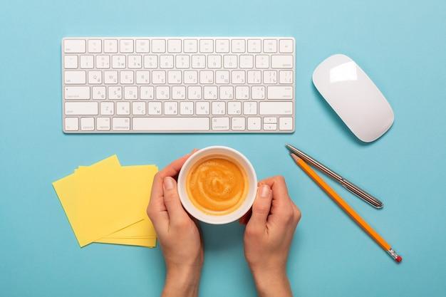 Widok z góry biznesowego miejsca pracy z filiżanką kawy. pusty obszar roboczy na niebieskim tle tabeli
