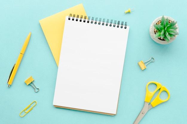 Widok z góry blatu z notatnikiem i nożyczkami