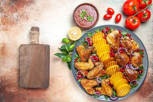 Widok z góry bliska kurczak sos kurczaka z ziemniakami i granatem pomidory deska do krojenia