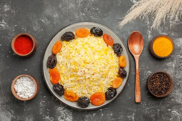 Widok z góry bliska miski ryżu kolorowych przypraw łyżka talerz ryżu z suszonymi owocami