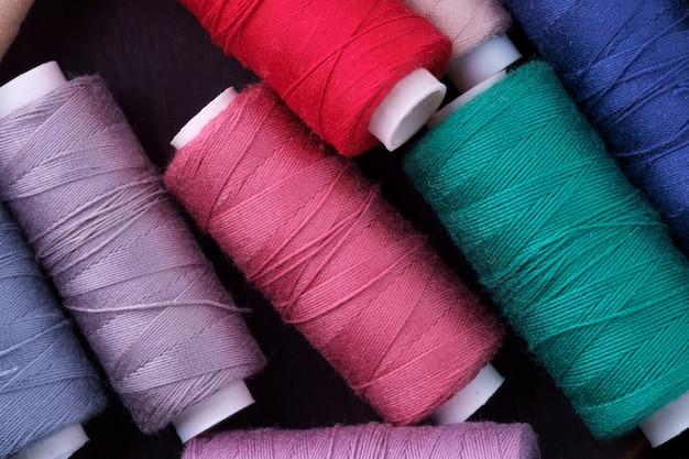 Widok z góry bliska rozrzuconych kolorowych cewek bawełnianych nici